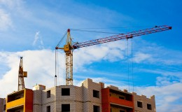 Two cranes and house construction
