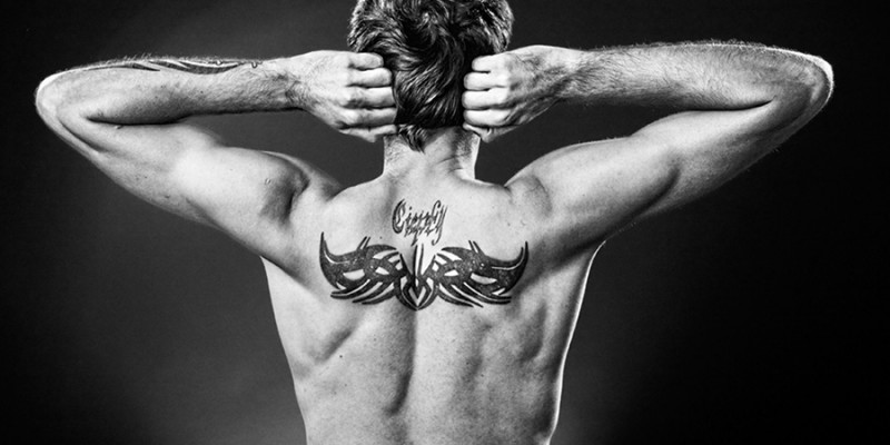 Man showing tatoo on his back made in studio