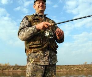 smiling men fishing with spinning