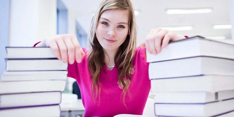 in the library – pretty, female student with laptop and books wo