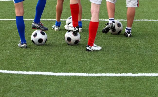 Soccer players with his foot on a football