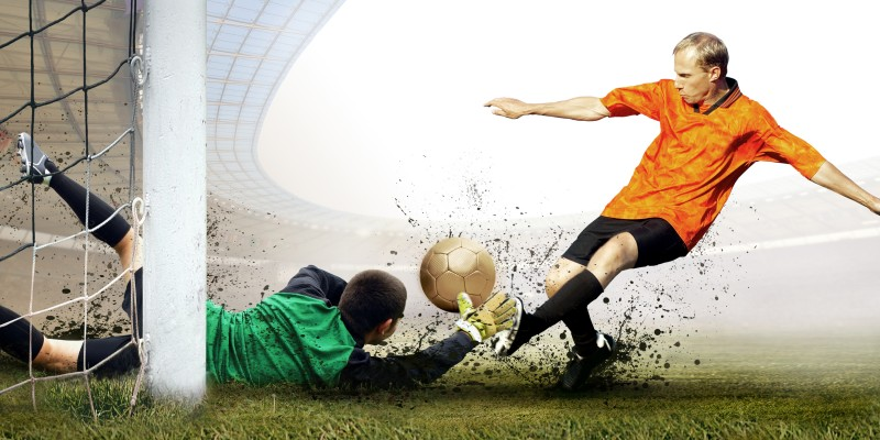 Shoot of football player and jump of goalkeeper on the field of