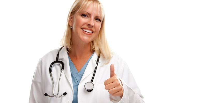 Friendly Female Blonde Doctor or Nurse with Thumbs Up Isolated on a White Background.