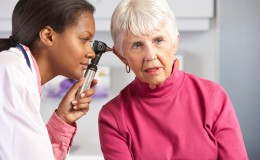 Doctor Examining Senior Female Patient's Ears