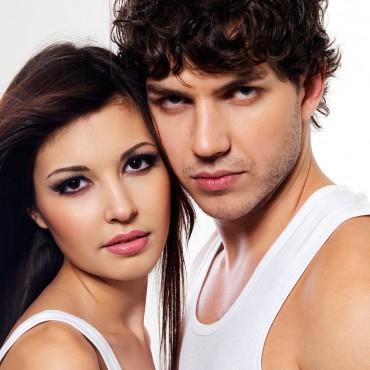 Two young beautiful lovers flirting. Posing at studio